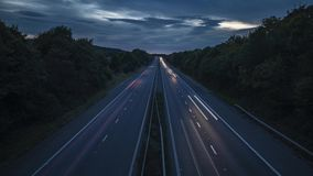 Rural motorway at twilight time lapse. Speeding vehicles on busy rural motorway at night. Time lapse sequence transition from twilight to night stock video