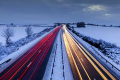 Rural Motorway at Winter in UK. Light trails of moving cars on rural motorway in snow at winter stock photo