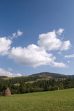 Rural mountain landscape. Beautiful blue sky and green grass with hayrick royalty free stock photography