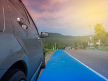 Rural mountains landscape with hills, mountains, road, blue summer sky with clouds and sun and car parked at the roadside during a. Trip Royalty Free Stock Photography