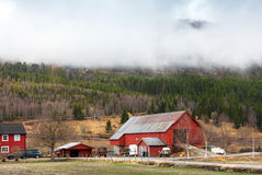 Rural Norwegian landscape with red wooden houses. And clouds on hills Stock Images