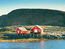 Rural Norwegian landscape, traditional red and white wooden house. On rocky island. Suny spring day with smooth water level in bay stock photography