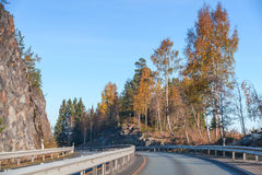 Rural Norwegian road goes near rocks Stock Images