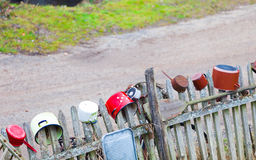 Rural. Old colorful pots dishes on wooden fence outdoor. Stock Images