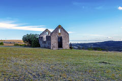 Rural Old  Derelect Farm Building on Dry Winter Landscape. Rural old abandoned derelect farm building on dry winter landscape against blue cloudy sky in Lake Stock Images