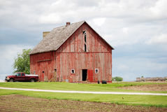 A rural old, red barn with a red pickup truck. Stock Photos