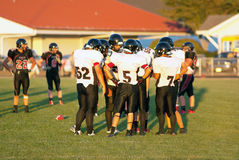 A rural Oregon high school foot ball team in a huddle