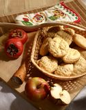 Rural pastry food. Cookies, two apple and persimmons, shoehorn.  Rural pastry food Stock Image