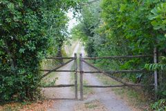 Rural path with closed wooden gate in Italian countryside. A closed wooden gate leads to a country road or path in the woodsy green area in central Italy Stock Photo