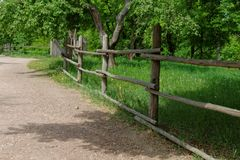 Rural path enclosed with lath fence at summer Stock Photos