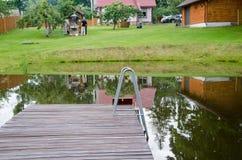 Rural pond with large plank bridge village yard Stock Photo