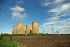 Rural power station. The cooling towers of a power station against a blue sky stock image