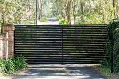 Black metal driveway entrance security gates set in brick fence Stock Images