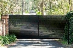 Black metal driveway entrance security gates set in brick fence. Rural property driveway entrance security gates set in brick fence Stock Images