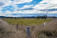 Rural property with fenceline in foreground. Rural property taken from fenceline corner.  Mountain range in the distance with overcast sky Stock Images