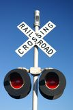 Rural rail road crossing sign with lamps. This is a typical, reflective, rural rail road metal crossing sign mounted on a wooden post found at a remote road stock photography