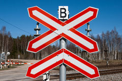 Rural railroad crossing sign. Red-white railway sign against a blue sky Stock Images