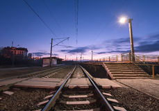 Rural railway station at night with blue sky. Railroad Stock Images