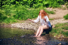 Rural red-haired girl  on the river Stock Photo
