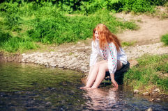 Rural red-haired girl  on the river Stock Photos
