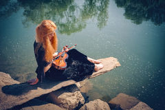 Rural red-haired girl with a violin Stock Photos