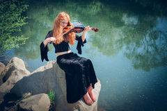 Rural red-haired girl with a violin Royalty Free Stock Photos
