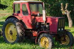 Rural red old farm tractor outdoor Royalty Free Stock Image
