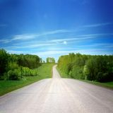 Rural road. And blue sky Royalty Free Stock Photo