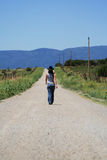 Rural Road. A woman with a cowboy hat walks down a long, dirt road toward distant blue mountains Royalty Free Stock Photo