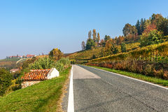 Rural road and autumnal hills in Piedmont, Italy. Royalty Free Stock Images