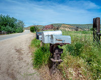 Rural road with a barn and mail boxes Stock Photos