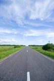 Rural road and cloudy sky Royalty Free Stock Photos
