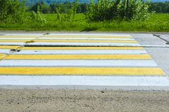 Rural road of concrete slabs. Pedestrian crossing over a concrete road. White and yellow stripes on the road stock images