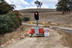 Rural road construction with traffic light and signs Stock Image