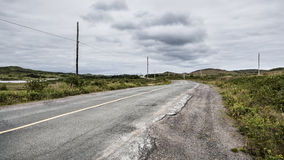 Old Road Fades into the Horizon Underneath a Dark Cloud Formation. A rural road with cracked pavement leads to the horizon.  Greenery runs alongside the road and Royalty Free Stock Image
