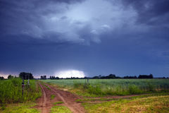 Rural road and dark storm clouds Stock Image