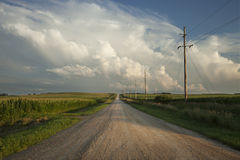 Rural road with dramatic clouds in southern Minnesota at sundown. Rural Minnesota road with dramatic clouds at sundown Royalty Free Stock Images