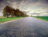 Rural road. Empty straight country road under cloudy sky Stock Photo