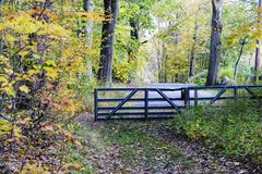 Gated entry. Rural road ending at  bent metal gate Royalty Free Stock Photos