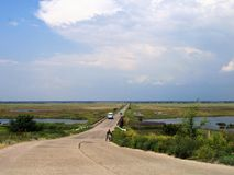 Summer road with cars. Rural road through the estuaries under the blue sky and white clouds on a warm sunny day Stock Image