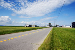 Rural road and farms Stock Photos