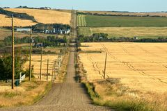 Rural road and farms in fall. A gravel road crossing a small valley with grain fields and farms on the sides Royalty Free Stock Photos