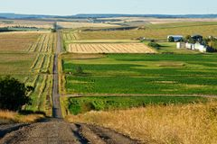 Rural road and farms in fall. A gravel road crossing a small valley with grain fields and farms on the sides Royalty Free Stock Photo