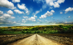 Rural road through the field in the mountains Stock Image