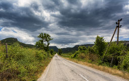 Rural road through fields with green herbs and grey sky  clouds Stock Photos