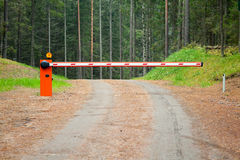 Rural road in the forest with closed barrier Royalty Free Stock Photo