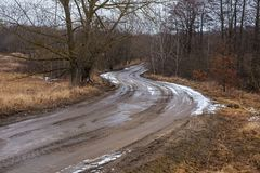 Rural road through the forest. Rural road through the forest with the remains of snow in early spring Royalty Free Stock Images