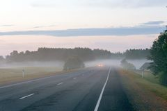 Rural road with headlights of car appearing through the fog. Rural road with headlights of car appearing through the afternoon fog. Summertime horizontal stock images