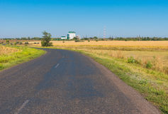 Rural road leading to grain elevator Royalty Free Stock Photos