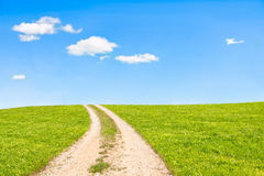 Rural road. Leading to the top of the green hill Royalty Free Stock Photos